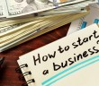 Notepad with how to start a business on the wooden table.